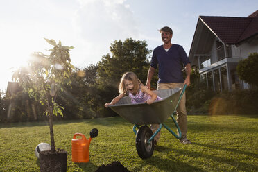 Father with daughter in wheelbarrow planting tree in garden - RBF002020