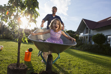 Father with daughter in wheelbarrow planting tree in garden - RBF002023