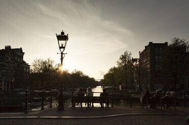 Netherlands, Amsterdam, view to town canal with relaxing people in the foreground by evening twilight - FCF000503