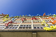 Germany, North Rhine-Westphalia, Duesseldorf, Sculptures Flossis climbing at facade of Roggendorf House, low angle view - THA000953