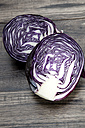 Two halves of red cabbage on dark wood - SARF001058