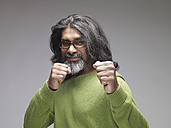 Mature man showing fists, looking confident, portrait - RH000400