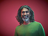 Portrait of smiling man in front of red background - RH000439
