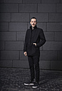 Portrait of black dressed man in front of grey background - RHF000440