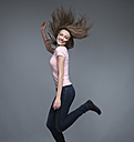 Portrait of smiling young woman dancing in front of grey background - RHF000425