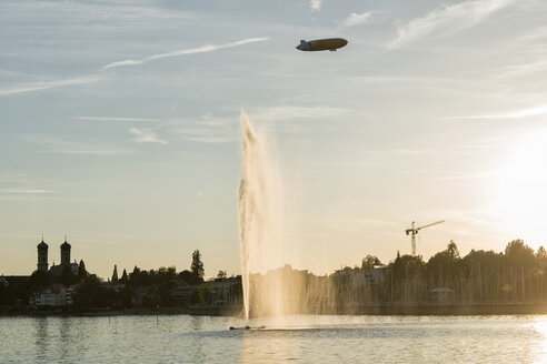 Germany, Baden-Wuerttemberg, Lake Constance, Friedrichshafen, fountain and zeppelin at sunset - SHF001761