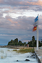 Switzerland, Thurgau, Lake Constance, Altnau, flags at harbor at dusk - SHF001669