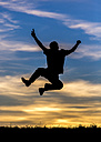 Germany, Silhouette of a man jumping at sunset - STSF000624