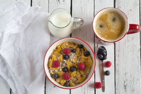 Bowl of granola with fresh fruits, cup of coffee and milk jug on white wood - SARF001077