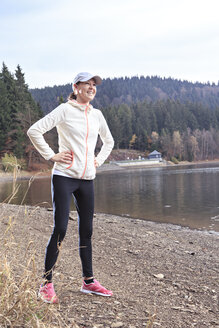 Smiling female jogger with hands in her hips standing at lakeshore - VTF000355