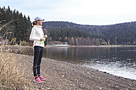 Female jogger with water bottle standing at lakeshore enjoying view - VTF000357