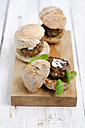 Three garnished bread rolls with patty and lamb's lettuce on wooden board and table - ODF000888