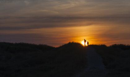 Denmark, Jutland, Lokken, mother and daughter walking in dune at sunset - JBF000210