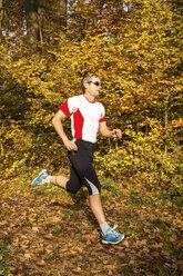 Man running in autumnal forest - STSF000641