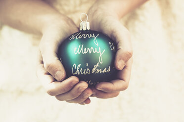 Girl's hands holding green Christmas bauble with the words 'Merry Christmas' - SARF001082