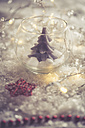 Glass with fir tree candle and red star on artificial snow - SARF001084
