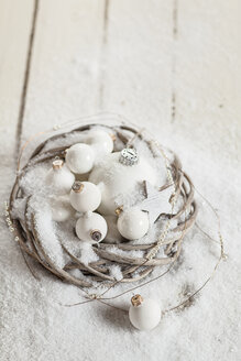 Wreath with white Christmas baubles, star and artificial snow on wood - SBDF001483