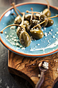 Pickled caperberries, Capparis spinosa, with sea salt on plate, studio - SBDF001471