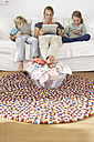 Mother and two children sitting on couch using smartphone and digital tablets ignoring pile of laundry - FSF000289