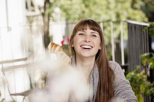 Portrait of happy woman having breakfast - FMKF001364