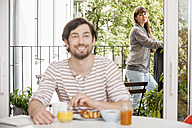 Man having breakfast with woman standing on balcony - FMKF001367