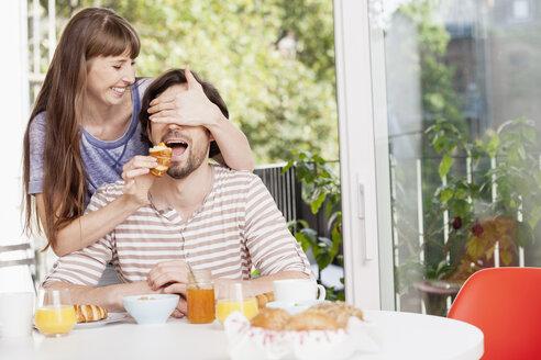Woman feeding man at breakfast table - FMKF001370