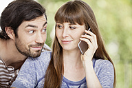 Man looking at woman on cell phone - FMKF001373