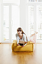 Relaxed woman reading magazine on ottoman at home - FMKF001381