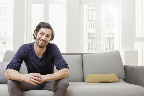 Smiling man sitting on sofa - FMKF001386
