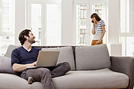 Couple using laptop and cell phone at home - FMKF001389