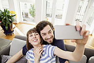 Happy couple taking selfie at home - FMKF001393