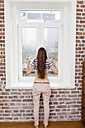Woman standing at window lifting her T-shirt - FMKF001401