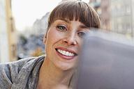 Smiling woman taking selfie on balcony - FMKF001436