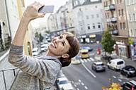 Smiling on balcony leaning back woman taking selfie - FMKF001414