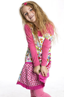 Portrait of smiling blond girl wearing colourful dress in front of white background - GDF000619