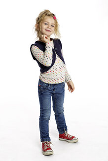 Portrait of flirtatious blond little girl standing in front of white background - GDF000629