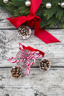 Advent wreath with red bow, fir cones and glass of sugar canes on wood - LVF002395