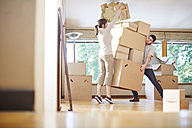 Couple moving house stacking boxes - ZEF002854