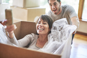 Playful couple moving house sitting in a box taking a selfie - ZEF002856