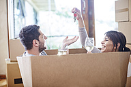 Couple moving house sitting in a box with key and wine glasses - ZEF002860