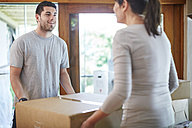 Couple moving house carrying a box - ZEF002866