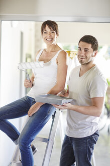Couple painting the wall in new home - ZEF002871