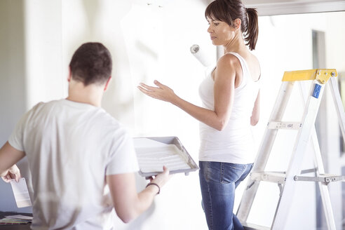 Couple painting the wall in new home - ZEF002873