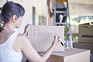 Couple moving house, woman writing on box - ZEF002878