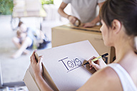Family moving house, woman writing on box - ZEF002880