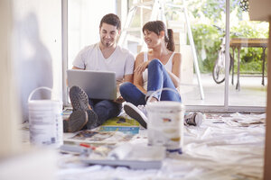 Couple with laptop having a break from renovating new home - ZEF002886