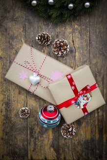 Wrapped Christmas presents, Christmas bauble and fir cones on dark wood - LVF002409