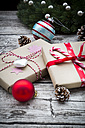 Wrapped Christmas presents, Christmas baubles and fir coner on wood - LVF002401