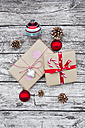 Wrapped Christmas presents, Christmas baubles and fir cones on wood - LVF002400