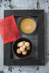 Bowl of butter tea, bowl of Tsampa balls,  red prayer flag and black picture frame on grey ground - MYF000727